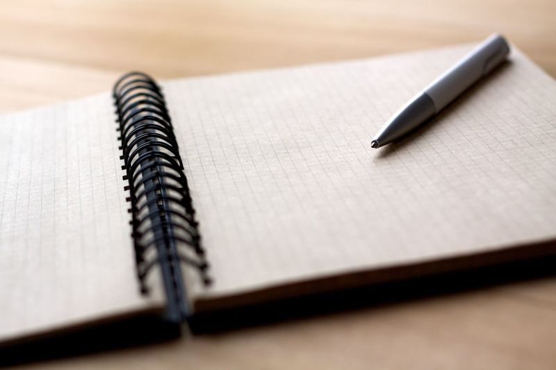 Close-up of pen on notepad at table