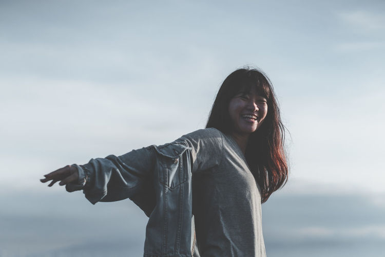 Asian woman traveler with jean jacket is smiling and raising her arms against cloud and blue sky Portrait Nature Outdoors Feeling Sunlight Rim Light Young Adult Travel Traveler Tourism Enjoying Life Happy Happiness Sea Of clouds Smiling Copy Space Good Outstretched Arms Laughing Fun Flying Sky Jeans Film Relaxing