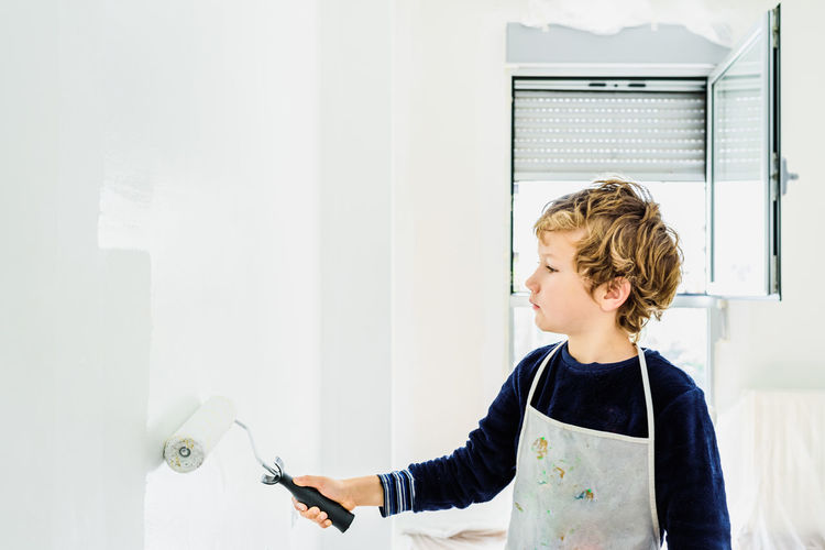 Cute boy painting wall at home