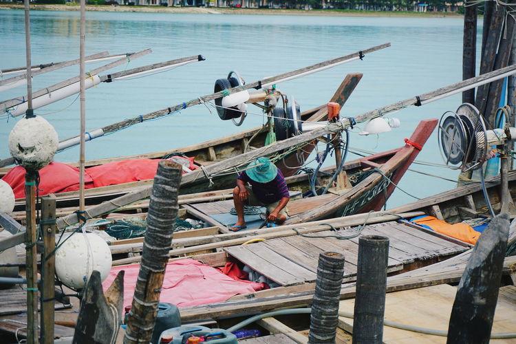 Fisherman on boat moored at lake