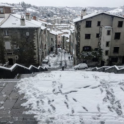 Snow covered road amidst buildings in city