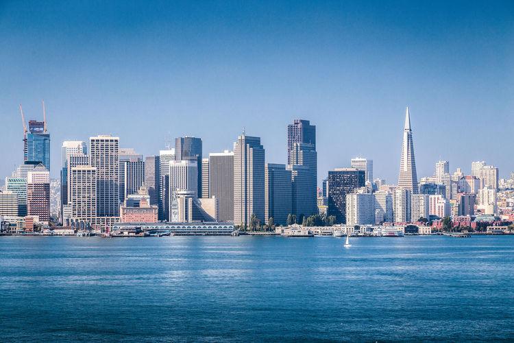 Sea by modern buildings against clear blue sky