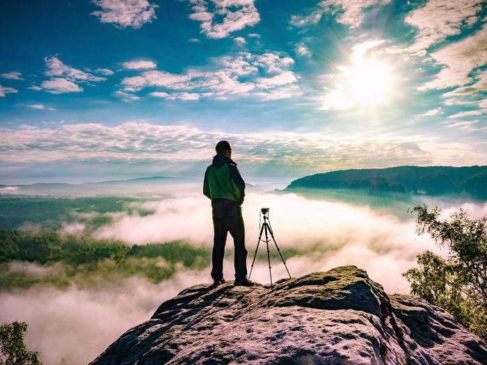 Man photographer staring into misty landscape of saechsische schweiz park. beautiful misty valley