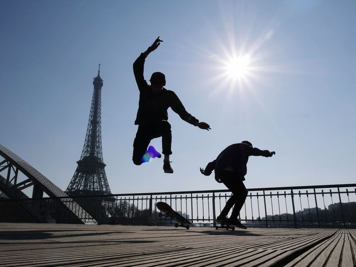 Low angle view of silhouette people skateboarding against eiffel tower on sunny day