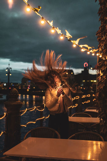Young Woman Tossing Hair While Holding Illuminated Lighting Equipment At Night