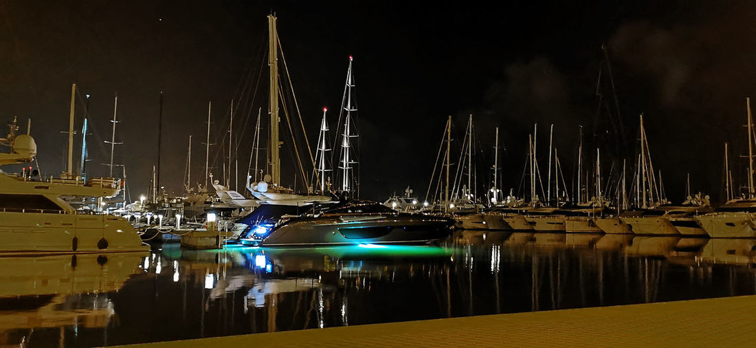 Sailboats moored at harbor against sky at night