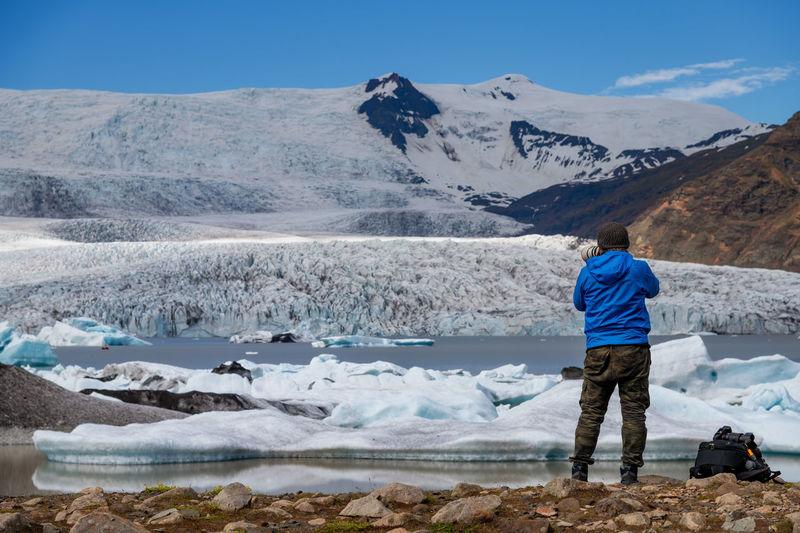 Rear View Of Man Photographing Snowcapped Mountain At Jokulsarlon Glacial Lagoon