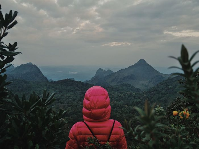 Woman in red jacket against mountains