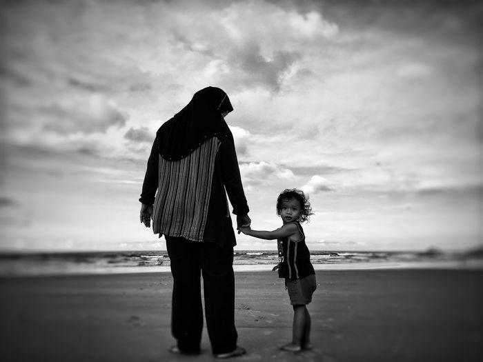 Portrait of girl with mother standing on shore at beach