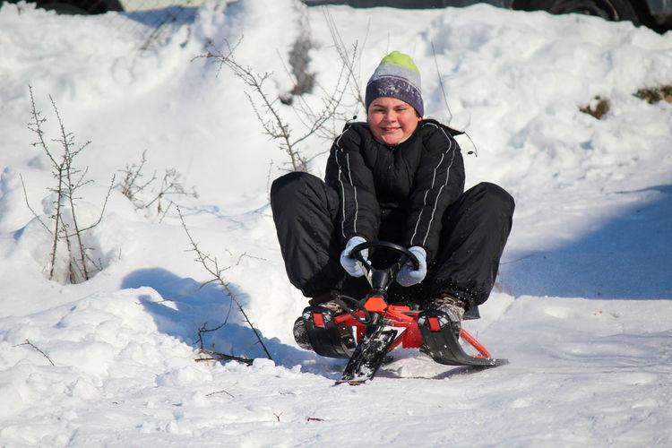 Full length of man sitting on snowy field