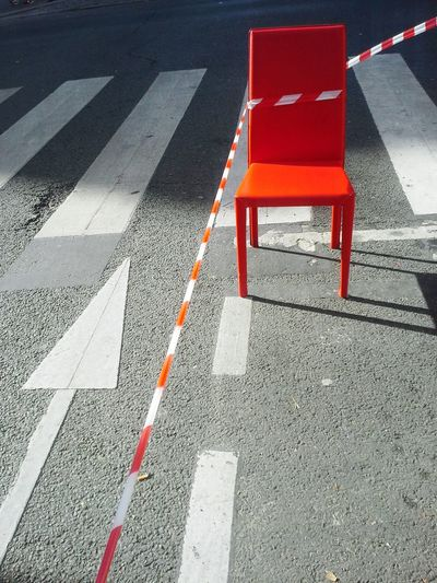 High angle view of orange chair by cordon tape on street