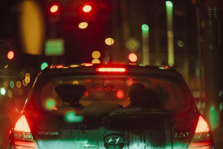 Close-up of illuminated traffic on street in city at night