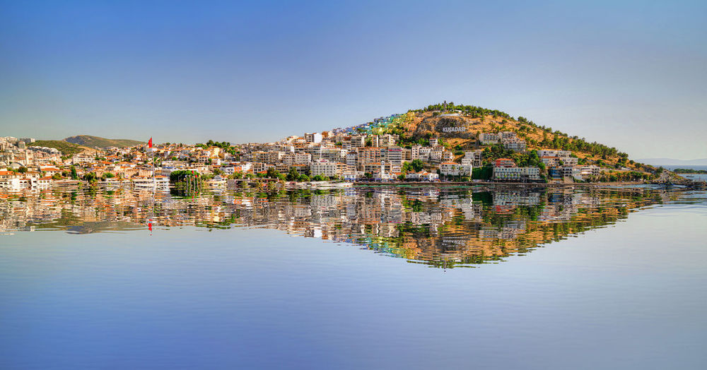 Panoramic shot of townscape by lake against sky
