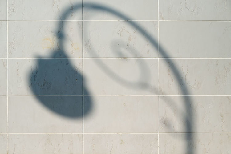 Shadow of lamp on tiled wall