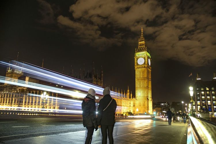 Rear view of people standing against big ben tower at night
