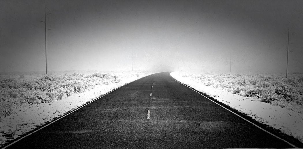 """Into The Abyss"" A black asphalt ribbon traverses a snowy landscape disappearing into a foggy realm. Spring Snow Blackandwhite Black & White Black And White Photography Foggy Snowy Snow Roadside Asphalt Direction The Way Forward Diminishing Perspective Transportation vanishing point No People Road Vignette"