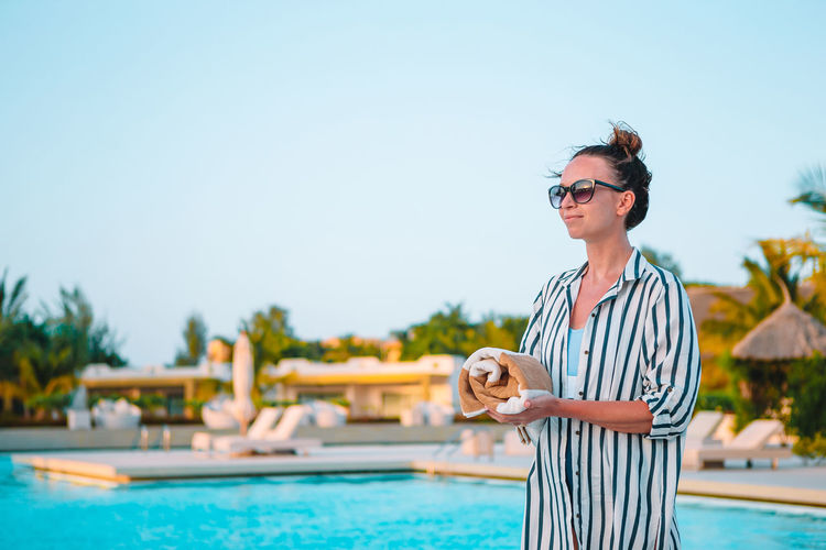 Man wearing sunglasses standing by swimming pool against sky