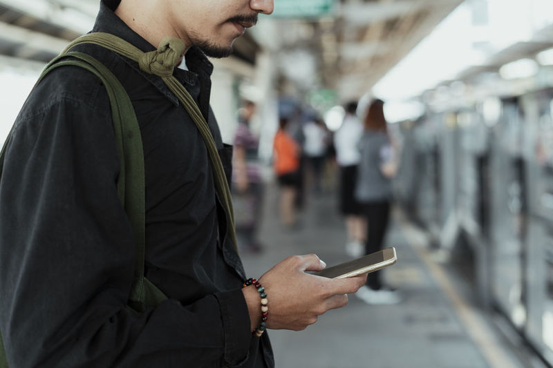 Midsection of man using smart phone while standing at railroad platform