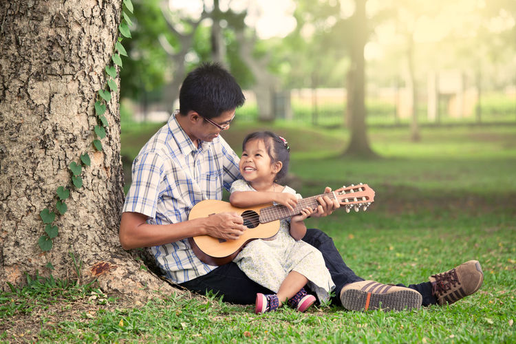 Father playing guitar while sitting with daughter on field at park
