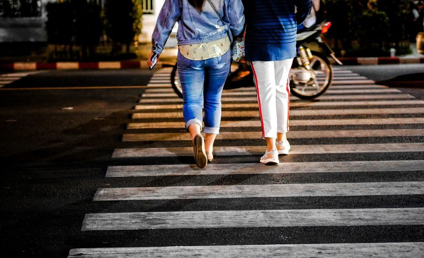 Low section of women walking on road in city