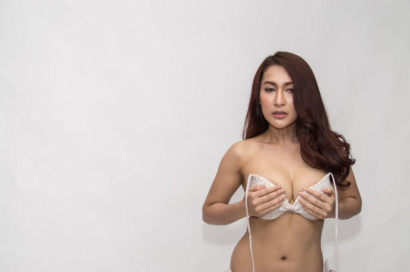 Young Woman In Bra Standing Against White Background