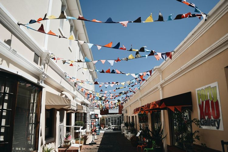 EyeEm Selects EyeEm Best Shots EyeEmNewHere Bunting Hanging Celebration Multi Colored Sky Building Exterior Architecture Streamer Flag Residential Structure Fluttering Patriotism The Street Photographer - 2018 EyeEm Awards