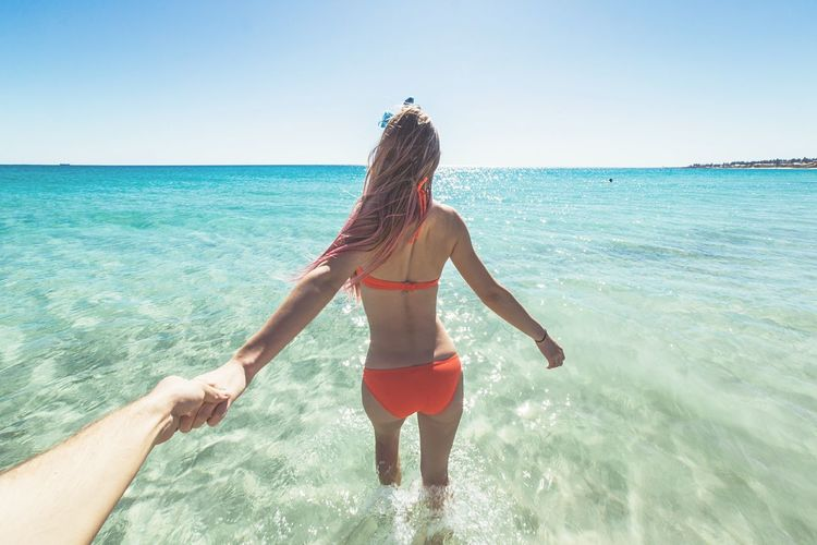 Rear View Of Woman At Beach Against Clear Sky