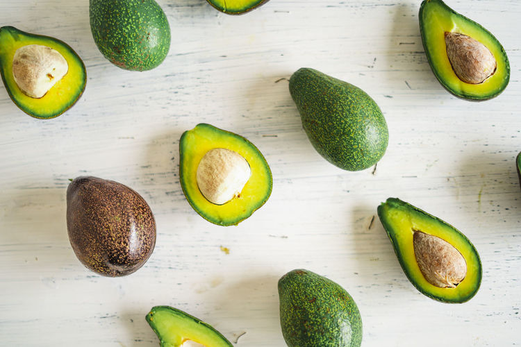 Close-Up Of Avocados On White Table Healthy Eating Food And Drink Food Wellbeing Fruit Freshness Avocado Still Life Green Color SLICE Table Indoors  Cross Section High Angle View Halved Kiwi No People Seed Kiwi - Fruit Vegetable