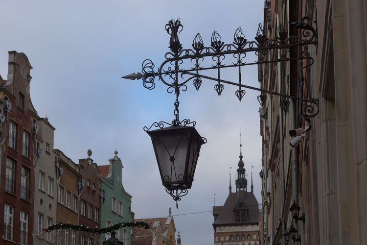 Low angle view of street light and buildings against sky