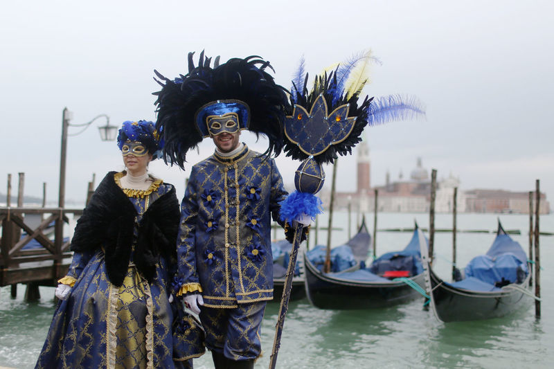 People wearing venetian masks and costume by grand canal